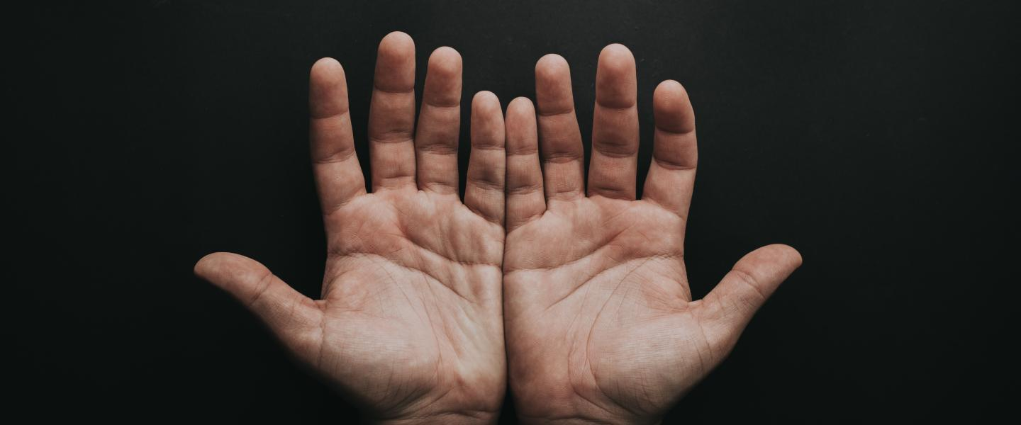 two hands palm forward against a dark background