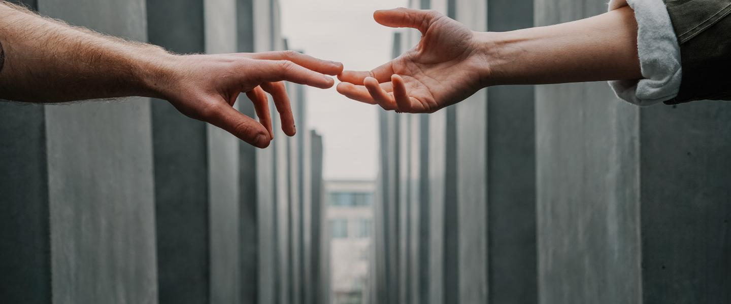 two hands reaching for each other