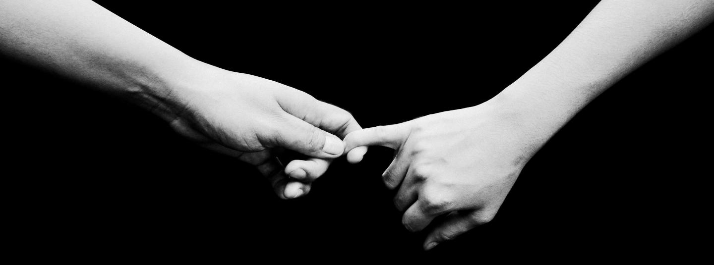 One person's hand holding another person's hand gently.
